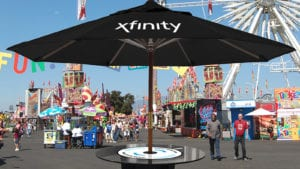 A large sun umbrella displaying the Xfinity logo.