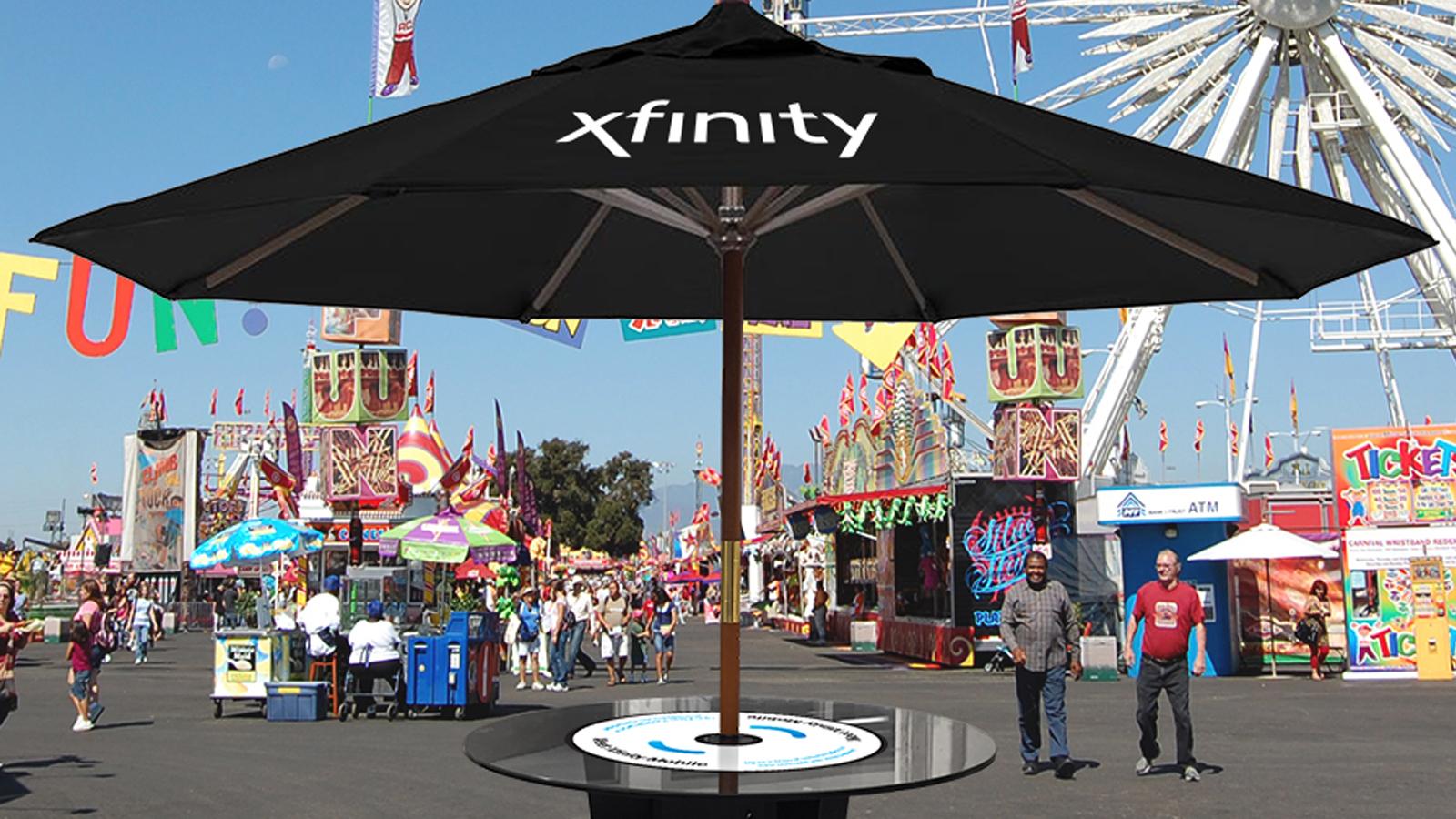A large sun umbrella displaying the Xfinity logo.