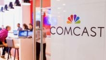 The Comcast logo on a glass door.