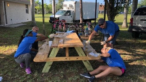 Comcast Cares Day volunteers refinish a picinic table.