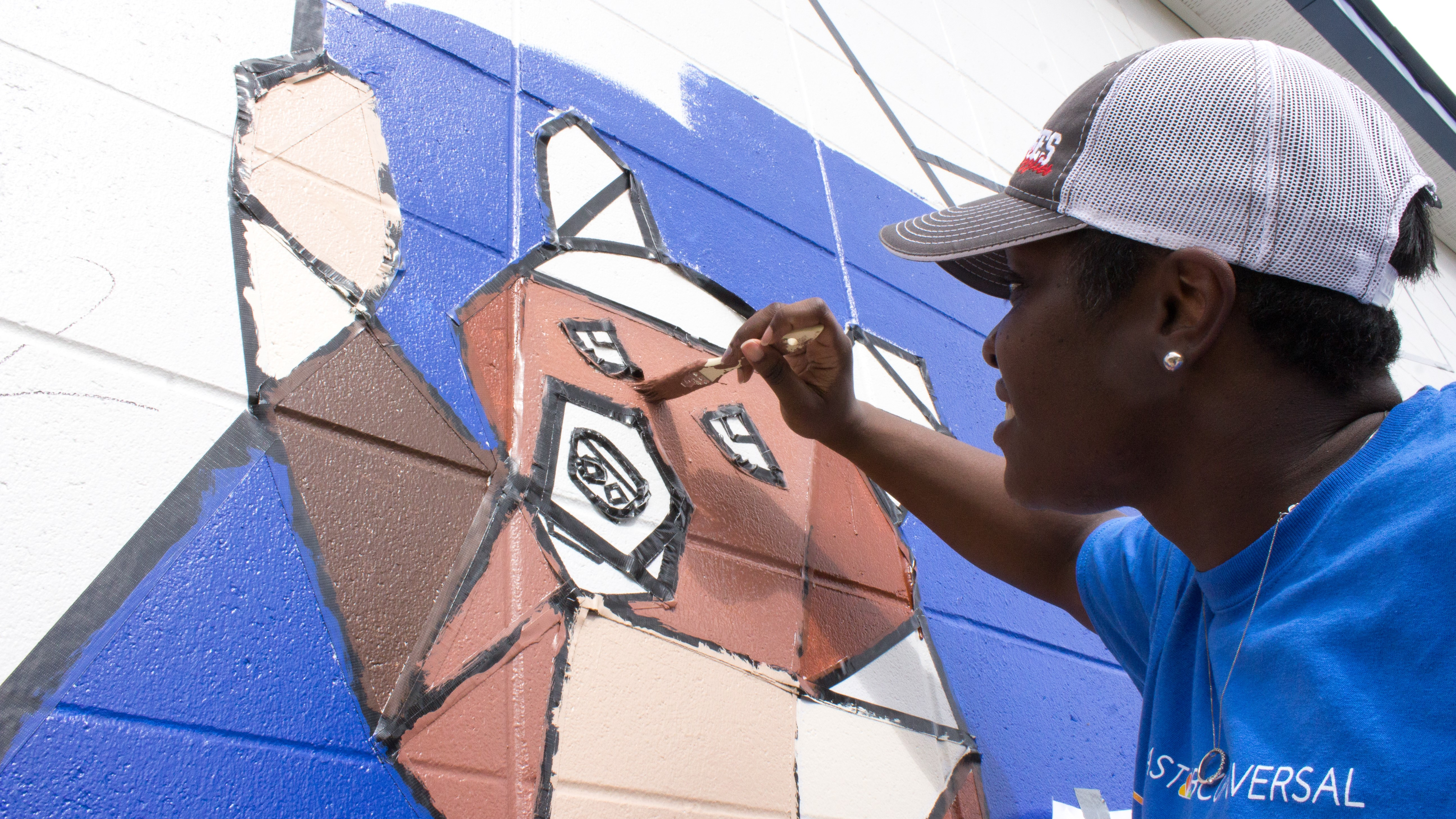 A Comcast Cares Day volunteer paints a mural.