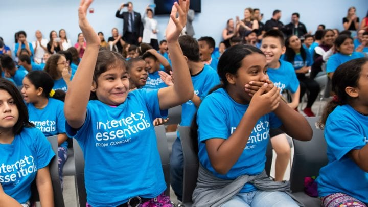 A group of children cheer at an Internet Essentials event.